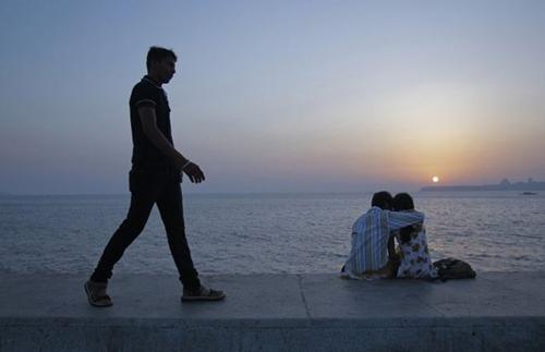 Một thanh niên đi qua đôi nam nữ đang hẹn hò ở Ấn Độ. Ảnh: Reuters