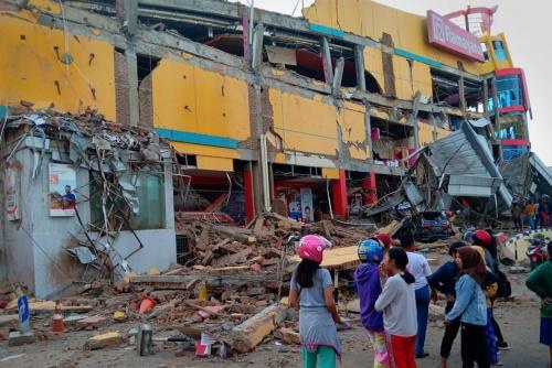 Người dân ở Palu đứng trước ngôi nhà bị sụp đổ sau trận động đất. Ảnh: Reuters.