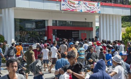 Người dân lấy hàng hóa trong một cửa hàng tiện lợi ở Palu ngày 30/9. Ảnh: AFP.