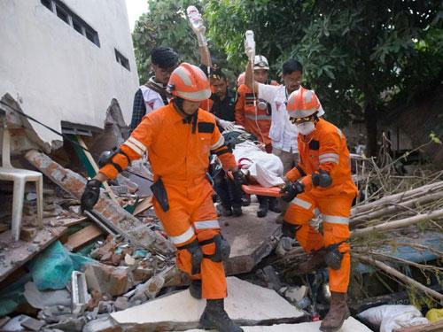 Lực lượng cứu hộ đưa một nạn nhân ở Palu ra khỏi đống đổ nát do động đất, sóng thần. Ảnh: Reuters.