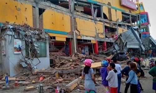 Người dân ở Palu đứng trước một ngôi nhà bị đổ sập sau trận động đất. Ảnh: Reuters.