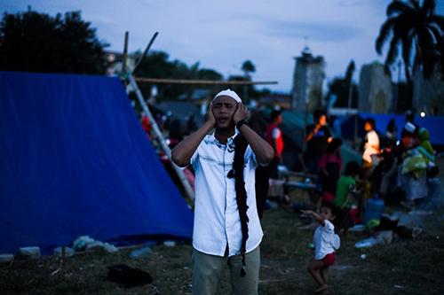 Một người đàn ông cầu nguyện tại lều tạm trú ở Palu hôm qua. Ảnh: AFP