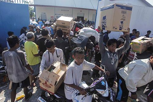 Những người hôi của tại một kho hàng ở Palu hôm 1/10. Ảnh: Reuters