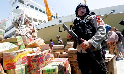 Cảnh sát canh gác hàng viện trợ tại cảngPalu hôm nay. Ảnh: Reuters