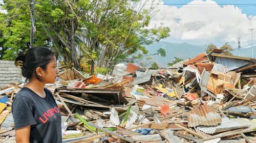 Ayu, 16 tuổi, đứng nhìn ngôi nhà giờ chỉ còn là đống đổ nát. Ảnh: SMH.