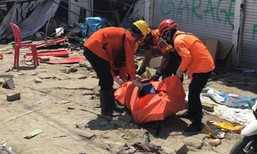 Đội tình nguyện viên chật vật nhét xác người phụ nữ trẻ vào trong túi. Ảnh: SMH.