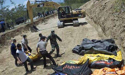 Lực lượng chức năng Indonesia đặt xác vào hố chôn tập thể hôm 1/10 tại Poboya. Ảnh: AFP.