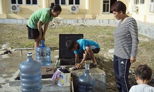 Một cậu bé (giữa) đang cố lấy nước sạch từ bể ngầm trong một trung tâm sơ tán tại Palu. Ảnh: AFP.