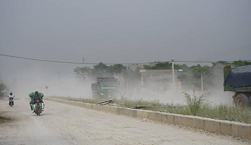Mỗi khi có xe tải đi qua là con đường mù mịt. Ảnh: Lam Sơn.