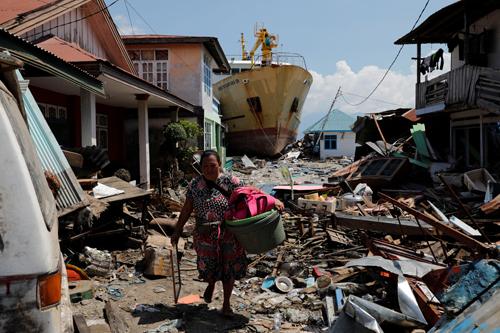 Người phụ nữ nhặt nhạnh những gì còn sót lại giữa đống đổ nát ở làng Wani, thị trấn Donggala hôm 2/10 sau thảm họa động đất, sóng thần. Ảnh: Reuters.