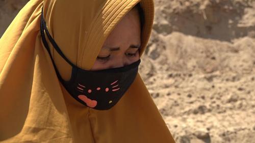 Surianti đứng cạnh hố chôn tập thể trên sườn đồi ở ngoại ô Palu, tỉnh Trung Sulawesi hôm 3/10. Ảnh: Sky.