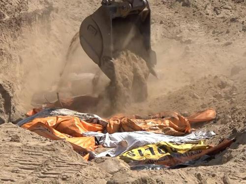 Máy xúc vùi đất lên thi thể các nạn nhân trong ngôi mộ tập thể sau động đất, sóng thần ở đảo Sulawesi, Indonesia. Ảnh: Sky.