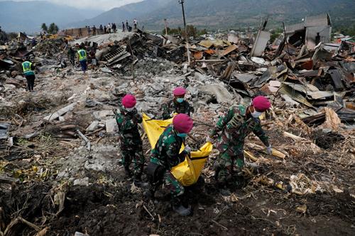 Binh sĩ Indonesia đưa thi thể ra khỏi những ngôi nhà bị sập ở Palu sau động đất hôm 4/10. Ảnh: Reuters.
