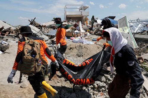 Nhân viên cứu hộ hôm nay đưa thi thể khỏi đống đổ nát ở làng Petobo. Ảnh: Reuters.