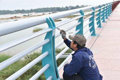 Công nhân sơn lan can cầu Thạch Bích. Ảnh: Phạm Linh.