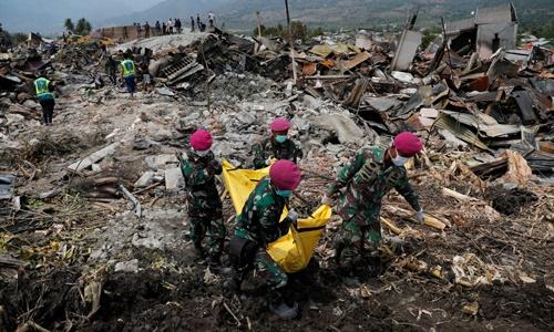 Binh sĩ Indonesia đưa thi thể nạn nhân ra khỏi đống đổ nát ở Palu hôm 4/10. Ảnh: Reuters.