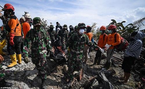 Binh sĩ Indonesia đưa thi thể ra khỏi đống đổ nát tại làngBalaroa hôm 6/10. Ảnh: AFP.