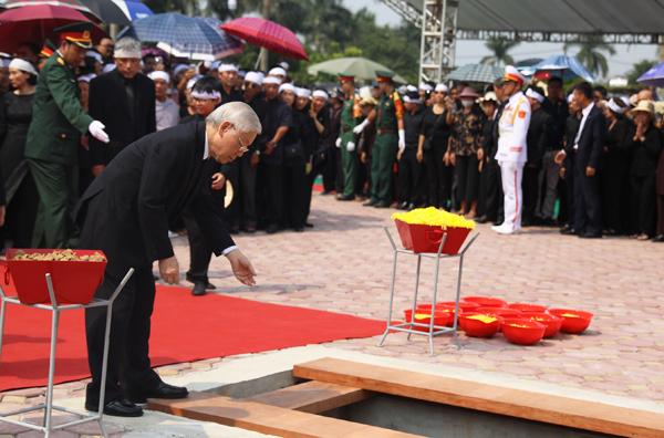 Tổng bí thư Nguyễn Phú Trọng rắc nắm đất xuống huyệt mộ. Ảnh: Ngọc Thành