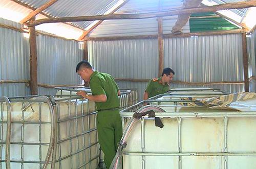 Cảnh sát kiểm tra các thùng đựng dầu nhớt lậu. Ảnh: Đức Hùng