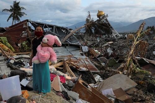 Người phụ nữ Palu ôm con gấu bông tại căn nhà bị phá hủy của mình hôm 7/10, nơi ba đứa con của cô đã thiệt mạng. Ảnh: Reuters.