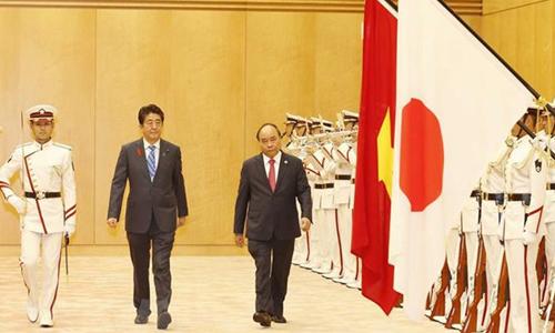 Thủ tướng Nhật Bản Abe, thứ hai từ trái sang, chủ trì lễ đón Thủ tướng Việt Nam, phải, trong chuyến thăm chính thức hôm nay. Ảnh: TTXVN.