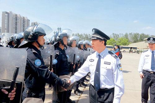 Mạnh Hoành Vĩ (thứ hai từ phải sang) bắt tay các cảnh sát chuẩn bị thực hiện nhiệm vụ gìn giữ hòa bình ở Libya. Ảnh: China Pictorial.