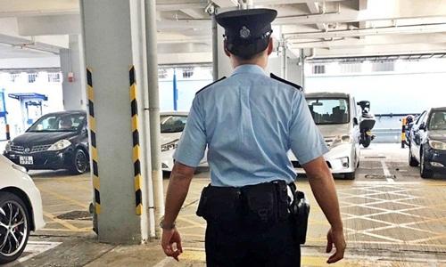 Viên cảnh sát đội mũ ngược tại một bãi đỗ xe ở Hong Kong. Ảnh: South China Morning Post.