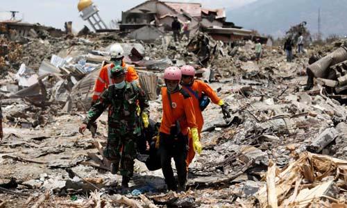 Các nhân viên cứu hộ và một sĩ quan đưa thi thể nạn nhân ra khỏi đống đổ nát ở thành phố Palu, Indonesia. Ảnh: Reuters.