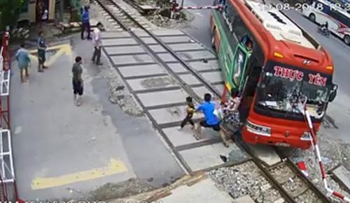 Xe khách mắc kẹt trên đường ray sau khi tông gãy cần chắn. Ảnh cắt từ clip.