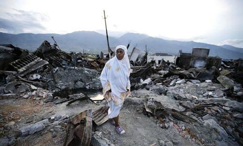 Một người phụ nữ đi trênnócmột ngôi nhà sụp đổ sau động đất và sóng thần ở Balaroa, Palu hôm 7/10. Ảnh: AP.