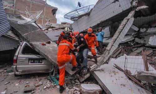 Đội tìm kiếm cứu hộ đưa một nạn nhân mắc kẹt sau khi động đất và sóng thần tấn công thành phố Palu, tỉnh Trung Sulawesi, Indonesia, ngày 28/9. Ảnh: Reuters.