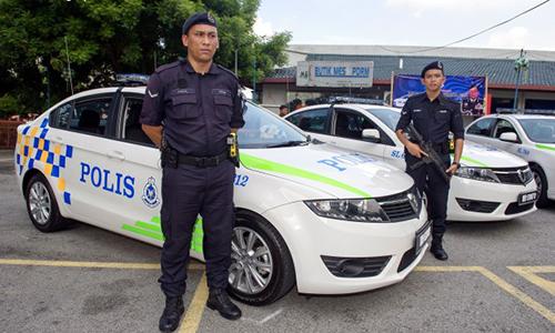 Cảnh sát Malaysia bên cạnh các xe tuần tra. Ảnh: Bernama