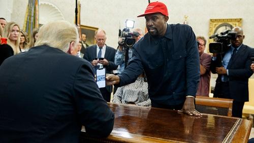 West đội mũ đỏ có dòng chữ Đưa nước Mỹ vĩ đại trở lại cho Trump xem hình ảnh máy bay chạy bằng hydro trên điện thoại của mình. Ảnh: Reuters.