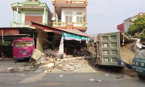 Chiếc xe tải lật sau khi tông sập ba ngôi nhà. Ảnh: L.S.
