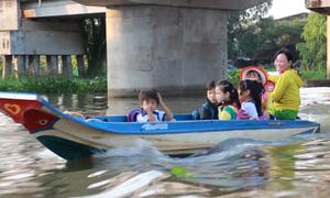 Trẻ em vùng lũ vượt đồng nước ngập bằng xuồng đến lớp