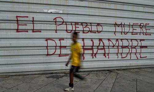 Một cậu bé đi qua tòa nhà viết dòng chữ Người dân đang chết đói ở thủ đô Caracas. Ảnh: AFP