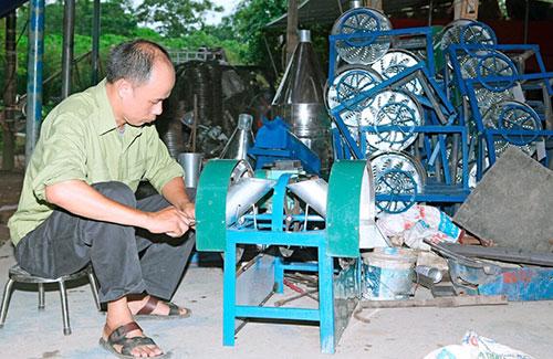 Ông Hà Kim Tới đang chế tạo máy ruôi sắn. Ảnh: KT.