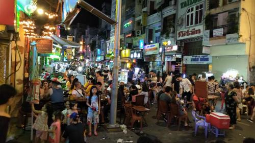 Người ngồi nhậugiữa lòng đường phố đi bộ Bùi Viện, ảnh chụp vào 23h30 ngày 13/10. Ảnh: Yến Thanh.
