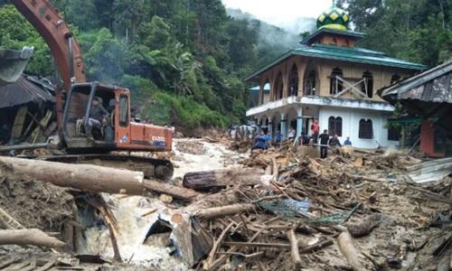 Nhân viên cứu hộ và dân làng dọn dẹp đống đổ nát và bùn lầy ở  làng Muara Saladi hôm 13/10. Ảnh: AFP.