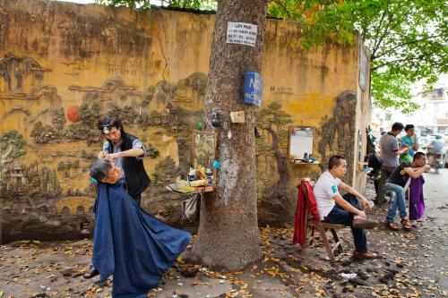 Góc phố với nhiều hàng cắt tóc vỉa hè ở Hà Nội. Ảnh: Catherine Karnow.