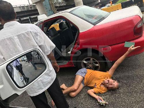 Người phụ nữ Việt nằm giữa đường khi cầu cứu một xe cảnh sát tuần tra trên cao tốc Damansara-Puchong, Malaysiahôm 11/10. Ảnh: NST