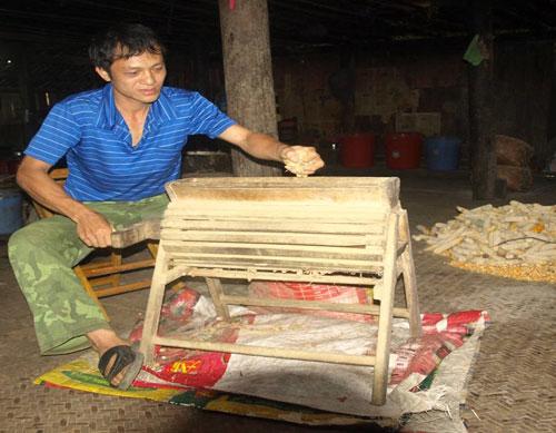 Anh Vương Hùng Nam bên chiếc máy bóc lạc quay tay bằng gỗ. Ảnh