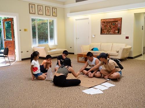 Kiều Ngân giới thiệu cho hai vị khách người Trung Quốc và các bạn nhỏ người Việt ở Hawaii cách chơi ô ăn quan. Ảnh: Thái Phạm