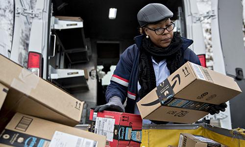 Nhân viên US Postal xếp bưu kiện lên xe tải tại một trung tâm vận chuyển và phân phối. Ảnh: Bloomberg.