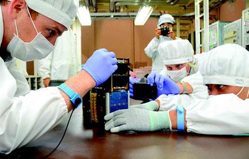 Các kỹ sư người Việt thực hành lắp ráp vệ tinh PicoDragon cùng chuyên gia tại Nhật Bản. Ảnh: VNSC.