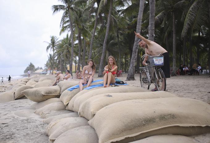 Bờ biển Cửa Đại sạt lở, du khách tắm nắng trên đê