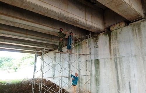 Các công nhân bắt giàn giáo kiểm tra vị trí nước nhỏ giọt dưới cầu chui. Ảnh: Phạm Linh.