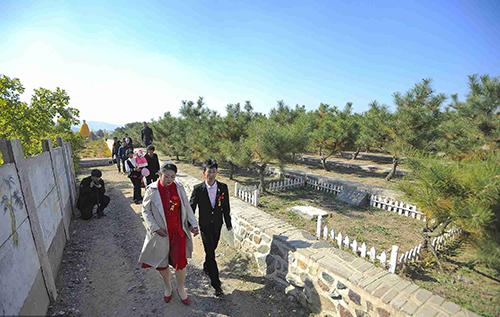 Cô dâu và chú rể nắm tay nhau đi trong nghĩa trang.Ảnh: CGTN