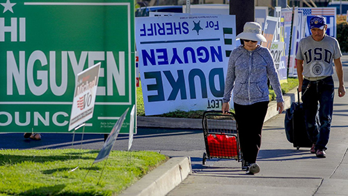Pedestrians walk past a row of political signs and posters along Bolsa Avenue in Westminster. In Orange County, 24 people of Vietnamese descent are running for public office. (Mark Boster / For The Times)