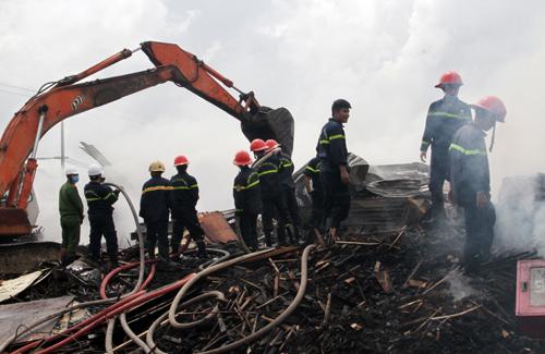 Nhiều cảnh sát phòng cháy Bình Định dập lửa ở kho dăm gỗ, trưa 23/10. Ảnh: Thạch Thảo.